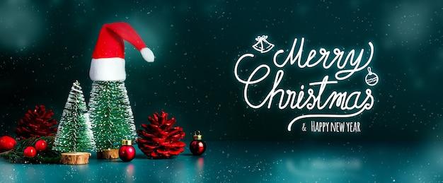 Buon natale e felice anno nuovo la neve che cade con l'albero di natale e il cappello rosso di babbo natale sul verde