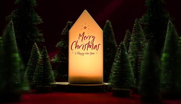 Testo di buon natale e felice anno nuovo sulla lampada di casa con albero di natale sul tavolo in tessuto di velluto rosso nell'umore della notte oscura