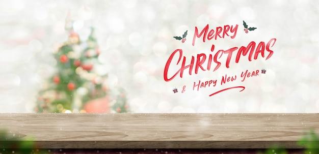 Buon natale e felice anno nuovo testo sul piano del tavolo in legno a sfocatura bokeh albero di natale decor con sfondo chiaro di stringa, biglietto di auguri invernale per la stagione invernale
