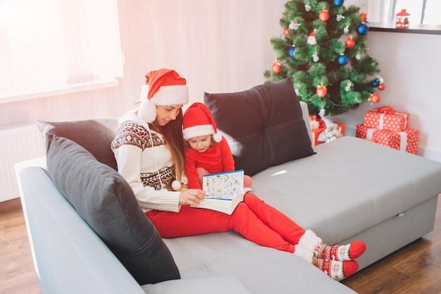 Buon natale e felice anno nuovo. la giovane donna si siede sul divano con la figlia