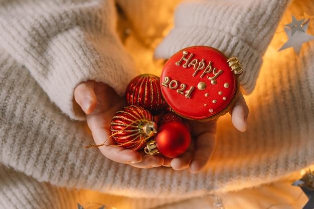 Buon natale e felice anno nuovo 2021. biscotti di panpepato in mano a un bambino. aspettando natale.