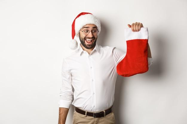 Buon natale, concetto di vacanze. l'uomo adulto felice riceve i regali in calza di natale, sembra eccitato, con indosso il cappello della santa, sfondo bianco.