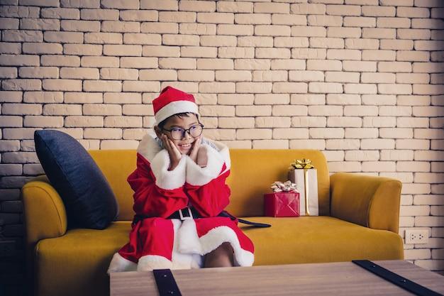 Buon natale little boy sedersi e attendere confezione regalo sul divano giallo in camera