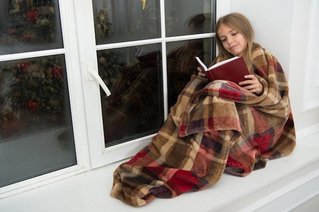 Buon natale. la bambina si diverte a leggere la storia di natale. il bambino ha letto il libro alla vigilia di natale. piccolo lettore avvolto in plaid seduto sul davanzale della finestra. libro illustrato per bambini. spirito magico di natale.