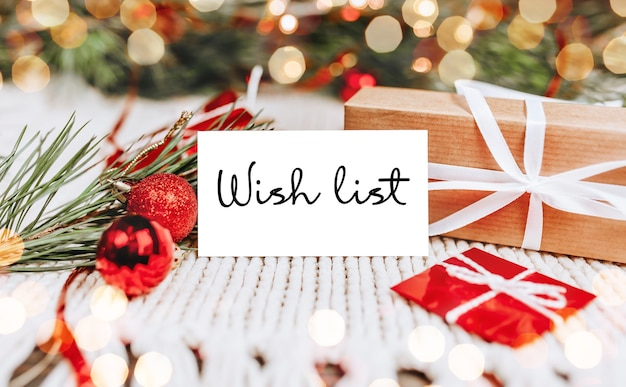 Buon natale e buon anno nuovo concetto con scatole regalo e biglietto di auguri con testo lista dei desideri