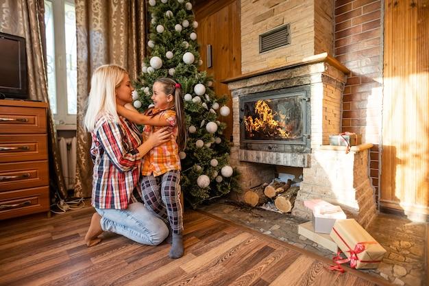 Buon natale. madre e figlia bambina che si scambiano i regali di natale