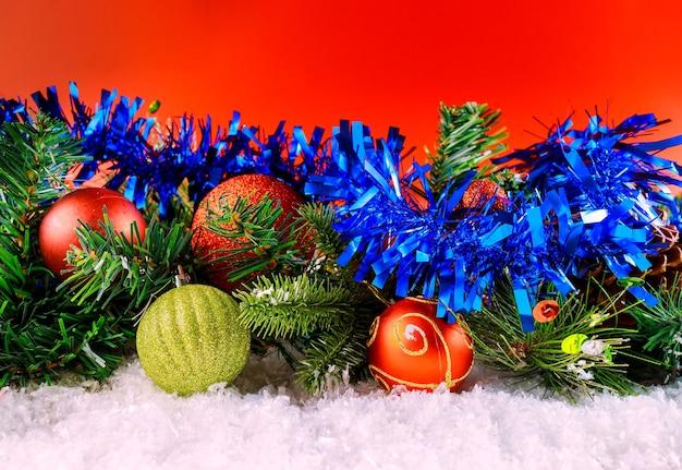 Buon natale e capodanno decorazione neve inverno nella palla fiocchi di neve sul ramo con pigna sfondo rosso