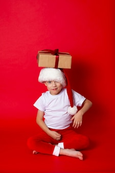 Buon natale. ritratto di un ragazzo carino con un berretto da babbo natale con scatole regalo su uno sfondo rosso. un posto per il testo. foto di alta qualità