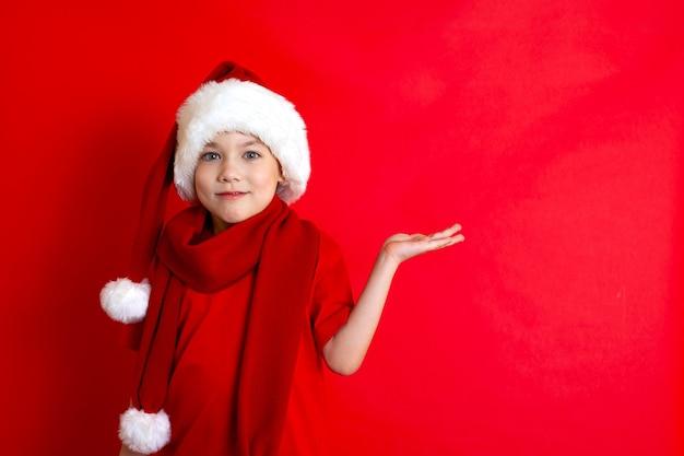 Buon natale. ritratto di un simpatico ragazzo allegro con un berretto natalizio in una maglietta rossa su sfondo rosso. un posto per il testo. foto di alta qualità