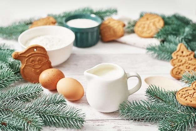 Buon natale, gustosi biscotti allo zenzero fatti in casa. ingredienti per cucinare la cottura, utensili da cucina, pan di zenzero. cartolina d'auguri di felice anno nuovo. tavolo di natale. abete, pino.