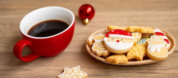 Buon natale con biscotti fatti in casa e tazza di caffè sul fondo della tavola in legno. vigilia di natale, festa, vacanza e concetto di felice anno nuovo