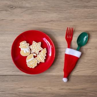 Buon natale con biscotti fatti in casa, forchetta e cucchiaio sul fondo della tavola in legno. concetto di natale, festa e felice anno nuovo