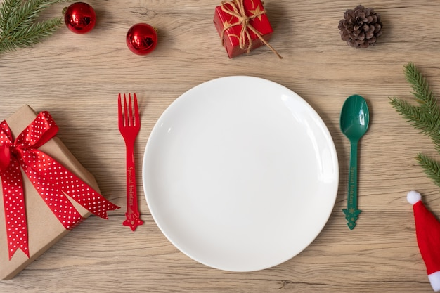 Buon natale con piatto, forchetta e cucchiaio sul fondo della tavola in legno. concetto di natale, festa e felice anno nuovo