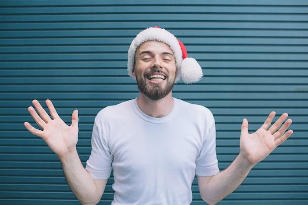 Ragazzo allegro e simpatico sta mostrando le sue mani e le dita sulla fotocamera. tiene gli occhi chiusi. guy indossa cappello di natale. è felice. isolato su strisce