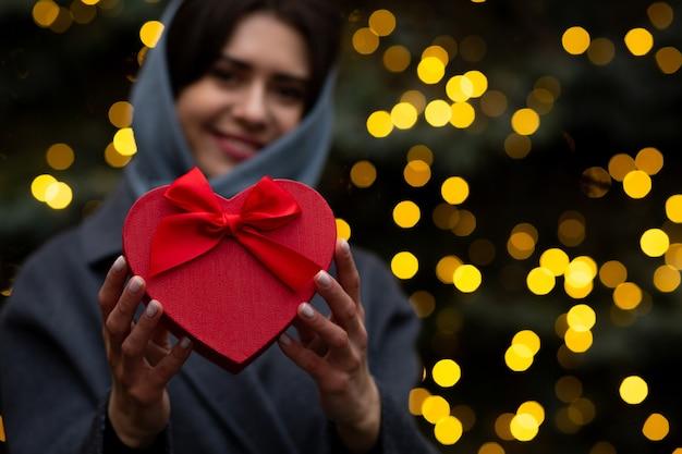 Donna allegra che tiene una scatola regalo di san valentino a forma di cuore con un fiocco su uno sfondo di luci sfocate. spazio per il testo