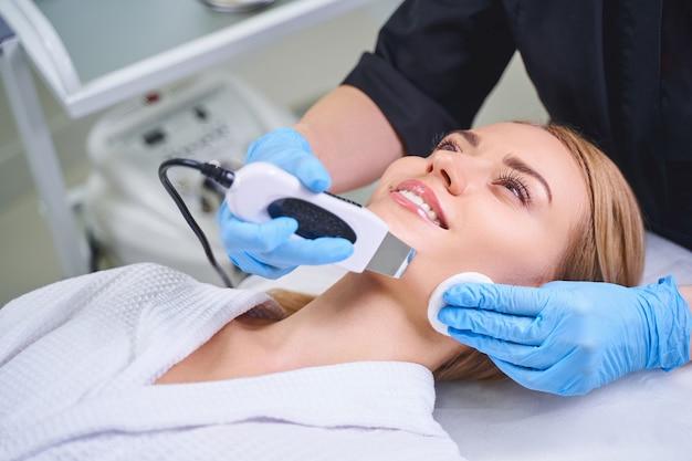 La giovane donna allegra si sta godendo un trattamento di bellezza nel salone mentre riceve il viso ad ultrasuoni da un cosmetologo esperto