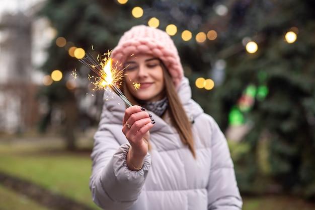 La giovane donna allegra indossa un cappello e un cappotto a maglia rosa che si divertono con le stelle filanti per la strada vicino all'albero di natale