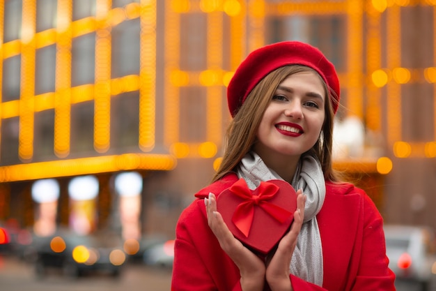 La giovane donna allegra indossa un berretto rosso e un cappotto che tiene una scatola regalo a forma di cuore con un fiocco su uno sfondo di luci sfocate. spazio per il testo