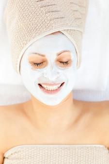 Giovane donna allegra con crema bianca sul suo viso rilassante su un lettino da massaggio