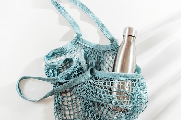 Borsa a rete con bottiglia d'acqua in metallo riutilizzabile e tazza su sfondo bianco.