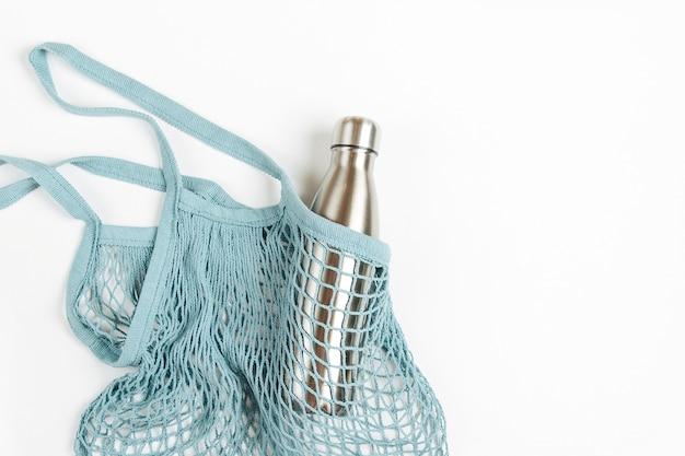 Borse a rete con bottiglia d'acqua in metallo riutilizzabile su sfondo bianco. stile di vita sostenibile.