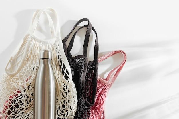Borse a rete con bottiglia d'acqua in metallo riutilizzabile su sfondo bianco. stile di vita sostenibile. Foto Premium