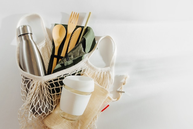 Borsa da mercato in rete con posate in bambù, tazza da caffè riutilizzabile e bottiglia d'acqua.