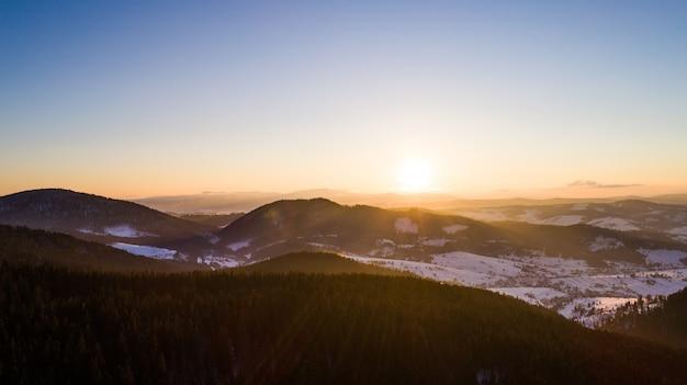Affascinante paesaggio rilassante di colline e montagne ricoperte di neve soleggiata calda sera d'inverno