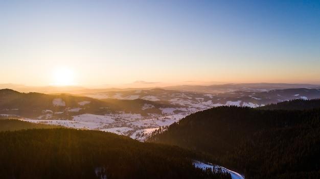 Affascinante paesaggio rilassante di colline e montagne coperte di neve soleggiata calda sera d'inverno