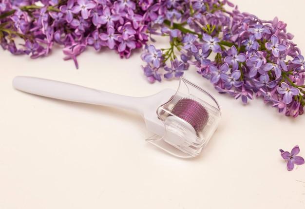 Mesoroller e fiori lilla su sfondo bianco. concetto di cura della pelle, antirughe, spa.