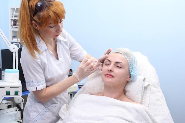 Mesoterapia. donna adulta che riceve la procedura antietà nel salone di bellezza.