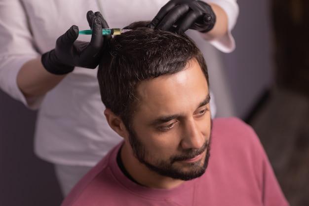 Mesoterapia per capelli. uomo attraente che riceve iniezioni nella sua testa. uomo che ha sessione di mesoterapia al salone di bellezza, terapista in guanto protettivo con siringa,