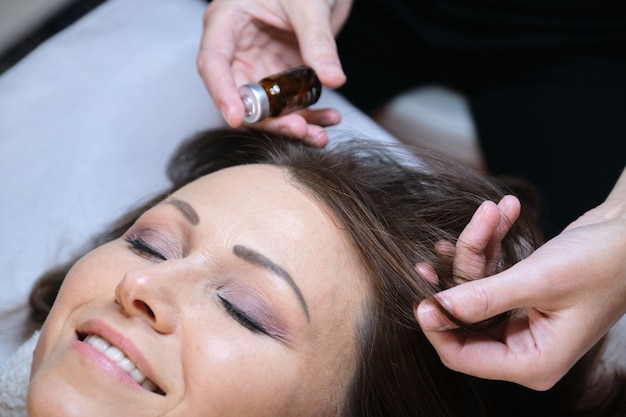 Mesoterapia, trattamento dei capelli. donna matura con problemi di perdita di capelli che riceve un trattamento in clinica, cosmetici per il rafforzamento e la crescita dei capelli