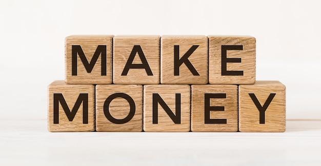 Il messaggio fa soldi sui cubi di legno della quercia sulla superficie bianca