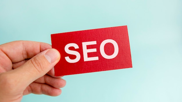 Messaggio sul cartellino rosso seo, nelle mani dell'uomo d'affari. seo - abbreviazione di ottimizzazione per i motori di ricerca. concetto di finanza.