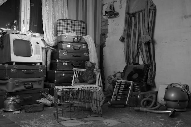 Vecchi oggetti spazzatura assortiti disordinati in una stanza. catturato in bianco e nero.