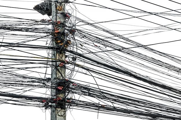 Caos disordinato di cavi con fili su palo elettrico su sfondo bianco, i tanti fili elettrici sui poli di potenza