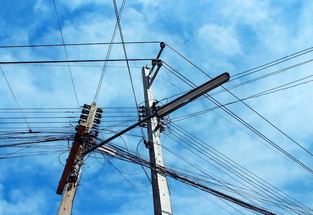 Cavi elettrici e cavi sudici sul palo elettrico sul fondo del cielo.