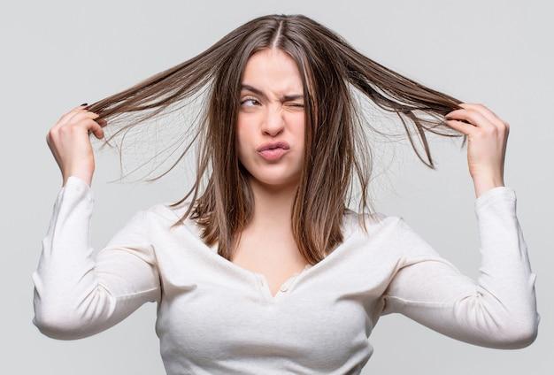 Capelli spettinati. donna castana con i capelli arruffati. ragazza che ha i capelli cattivi. brutta giornata per i capelli