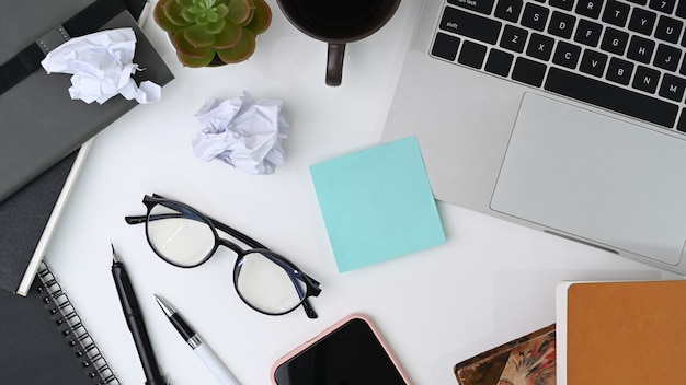 Scrivania da ufficio disordinata con computer portatile, nota adesiva, notebook e forniture.