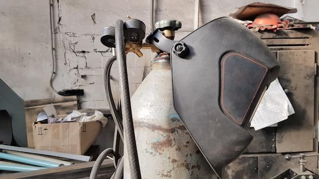 Vecchia maschera e attrezzatura di saldatura disordinate all'interno con il fondo dell'officina.