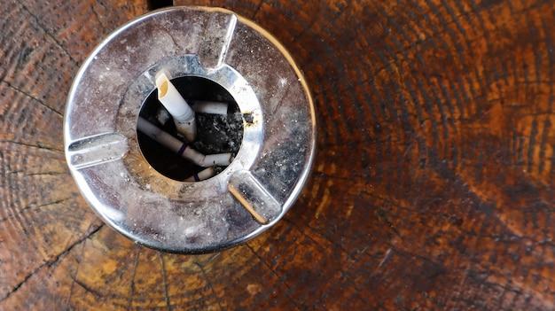Posacenere in metallo su una vista da tavolo in legno marrone. fumare in luoghi pubblici. disposizione piatta.