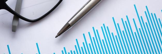 Penna a sfera in metallo e occhiali per la visione si trovano su documenti con grafici in ufficio
