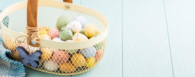 Cestino in metallo con uova di quaglia colorate di pasqua. concetto di vacanze di primavera con lo spazio della copia. banner