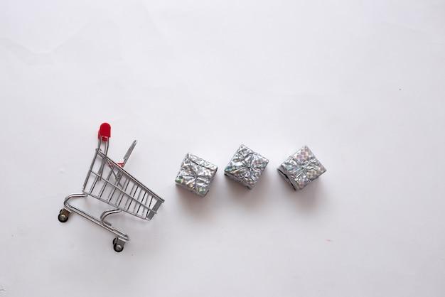 Cestino di metallo con piccoli regali lucidi su sfondo bianco con un posto per il testo