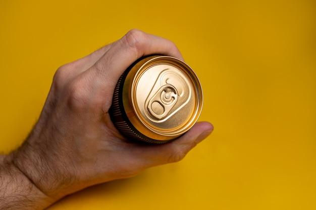 Lattina di birra in metallo in una mano d'uomo su sfondo giallo.