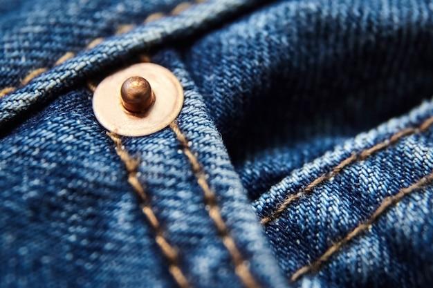 Bottone in metallo. chiuda sul fondo e sulla struttura delle blue jeans