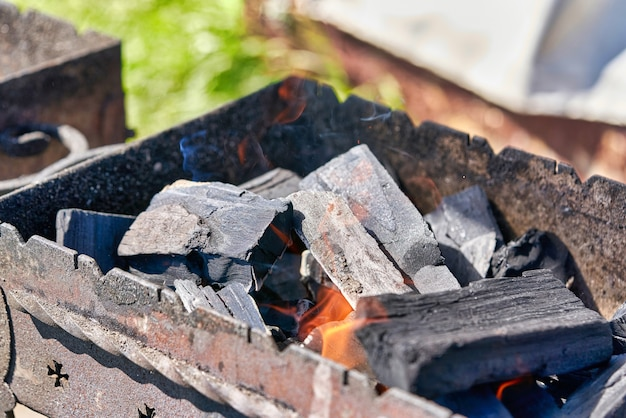 Braciere in metallo con carboni ardenti neri per la cottura. avvicinamento