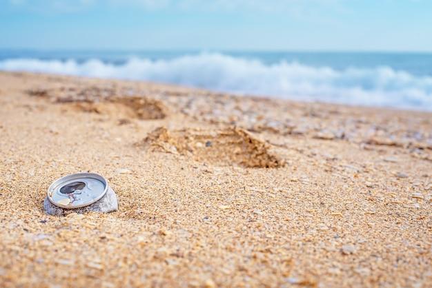 Una lattina di metallo lanciata da un'onda sulla spiaggia