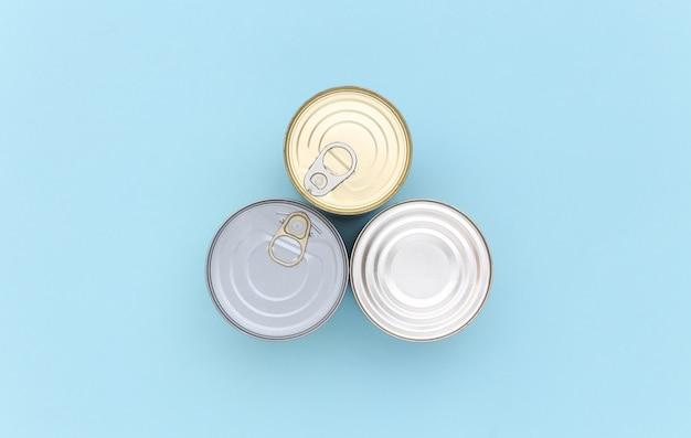 Lattine di metallo di cibo in scatola su sfondo blu. vista dall'alto